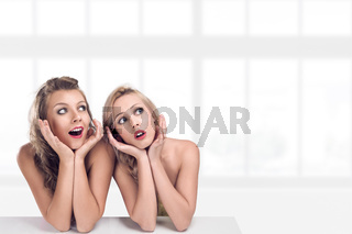 Two young surprised women looking up