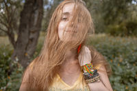 Attractive long haired blond girl boho style bracelets hide half of her face by hair