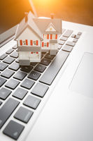 Miniature House And Laptop Computer Resting on Desktop.