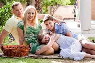 Lovable family of four relaxing during sunny day and looking at camera