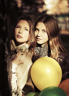 Two young fashion teen girls with a balloons in autumn park