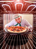 Chef cooking pizza in the oven.