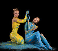 Two naked girls with bodyart sitting on the floor