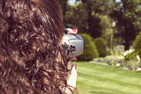 Girl taking photo with digital mirror camera closeup shot