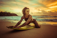 Beautiful woman with yellow surfboard on the beach over amazing sunset