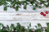 Snowy Christmas branches with red ornaments on rustic white wooden background