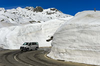 Car driving on the pass road between high snow walls across the St Gotthard Pass, Switzerland