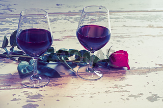 Two glasses of wine and a red rose