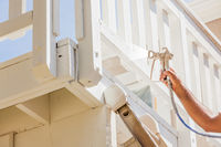 Professional House Painter Wearing Facial Protection Spray Painting Deck of A Home