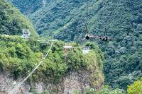 Cascades route, Banos, Ecuador - December 8, 2017: Tourists gliding on the zip line trip against the canyon