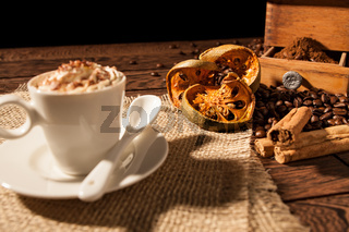 Close-up of coffee cup, dried orange fruit and cinnamon sticks