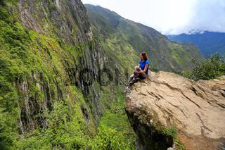 Young woman enjoying the view of Inca Bridge and cliff path near Machu Picchu in Peru