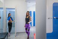 Pretty girls pose in locker room of sports center