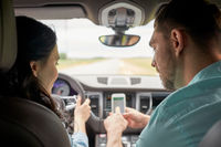 happy man and woman with smartphone driving in car