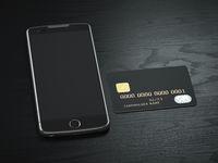 Smartphone with credit card ion black wooden desk background Mobile banking, e-commerce , business finance mock up concept.