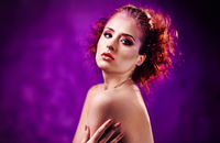 Portrait of beautiful young red-haired woman with a bright make-up