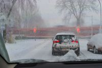 A car stands in the snowstorm in front of closed railway barriers, while a red passenger train passe