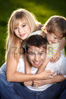 Happy couple and the child on a lawn
