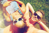 happy teenage couple lying on grass at summer