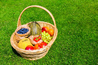 Wicker basket on grass filled with fruit