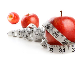 Red apples and measuring tape on white