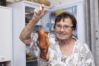 Happy senior woman holding smoked meat