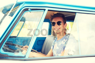 smiling young hippie man driving minivan car
