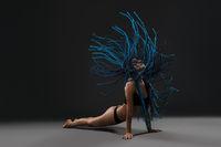Girl with blue dreadlocks photo against black wall