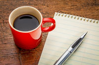 notepad with pen and coffee
