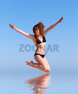 young beautiful woman jumps against the sea