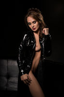 Sexy brunette in black bdsm style unbuttoned coat
