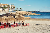 People sitting at the beach cafe in the Cabo Roig. Spain