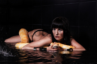 Beautiful woman lying with Python in water