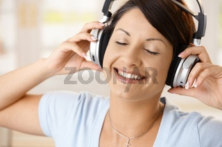 Happy woman enjoying music on headphones