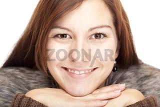 Schöne junge gesunde Frau stützt Kinn auf Hände und lacht