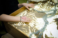 A little kids draws on sand, sand animation, Hands close up