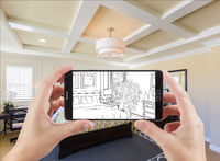 Hands Holding Smart Phone Displaying Drawing of Bedroom Photo Behind