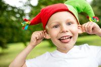 Fröhlicher Junge zieht sich an den Ohren