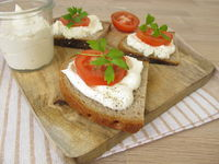 Piece of bread with whipped feta cream and tomato