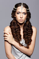Beauty portrait of young woman with diadem. Brunette girl with long hair braids and day female makeup on gray background