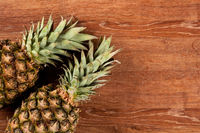 Two pineapples on a wooden background still life