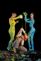 Nude girls pouring color on a man sitting on floor