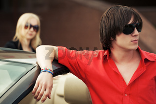 Young handsome fashion man in sunglasses standing by his convertible car