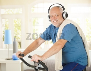 Active pensioner doing spinning with music