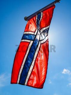 Norwegian flag up close, towards the sun on beautiful blue sky