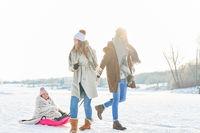 Eltern beim Spaziergang mit Kind im Schlitten