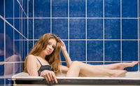 Side view of sexy woman in black lingerie sitting in a bath with her legs out in front of tiled wall of blue color vintage colorized image.