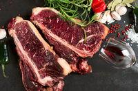 Raw aged steak and seasoning on dark background