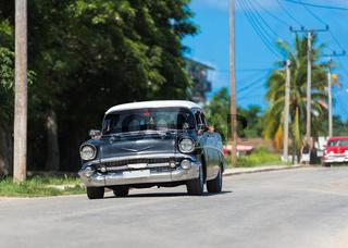 Amerikanischer schwarzer Oldtimer mit weißem Dach fährt auf der Strasse in Santa Clara Kuba