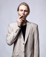 Young blond male model in beige man suit smoking